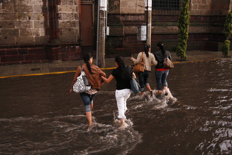 Ciudadanos de Guadalajara, tratando de cruzar una de las calles inundadas de la ciudad.