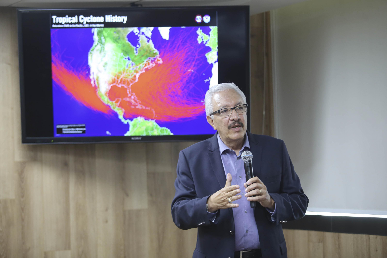 El investigador del Instituto de Astronomía y Meteorología de la Universidad de Guadalajara, Dr. Ángel Meulenert Peña, con micrófono en mano, explicando el historial de ciclones tropicales.