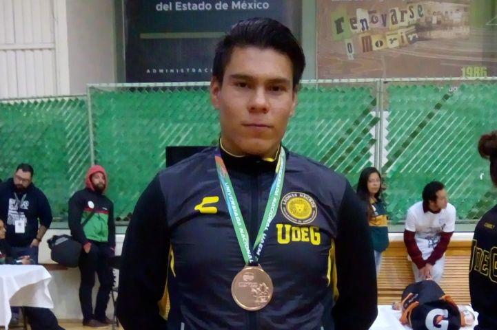 Alumno posa con la medalla que obtuvo en las competencias