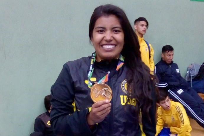 Una alumna de la UDG sostiene con orgullo su medalla obtenida