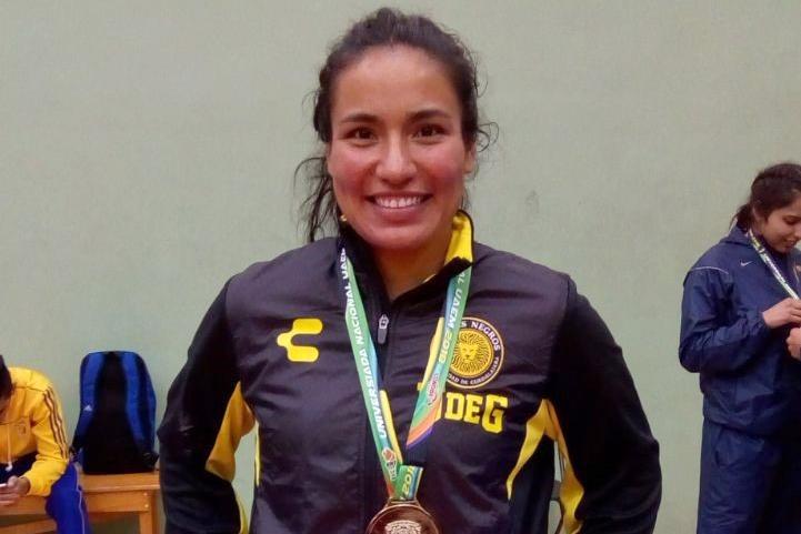 Una estudiante de la UDG posa con su medalla ganada en una prueba de la UNIVERSIADA