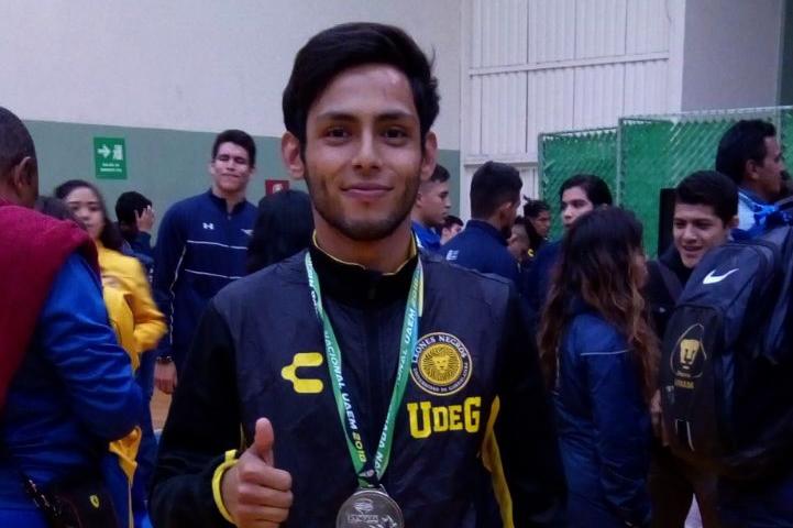 Un joven estudiante muestra su medalla al termino de la competencia