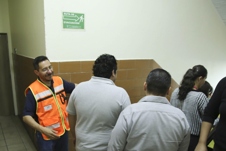Brigadista de la Universidad de Guadalajara, guiando al personal por la ruta de evacuación.