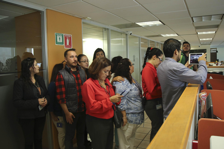 Personal administrativo de la Universidad de Guadalajara, atendiendo indicaciones para evacuar el edificio.