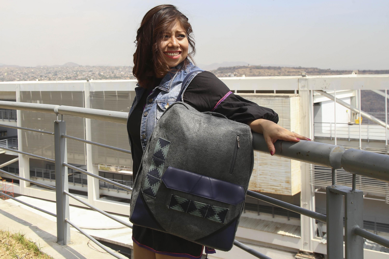 Nancy Gabriela Rojas Juárez, egresada de la licenciatura en Diseño de Modas del CUAAD; Modelando en uno de los barandales del centro universitario, una mochila diseñada por la misma que rescata tradición textil wixárika.