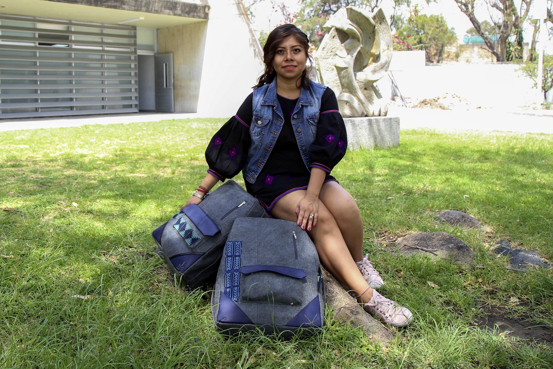 Nancy Gabriela Rojas Juárez, egresada de la licenciatura en Diseño de Modas del CUAAD; Modelando en los jardines del centro universitario, dos diseños de mochila que rescatan tradición textil wixárika.