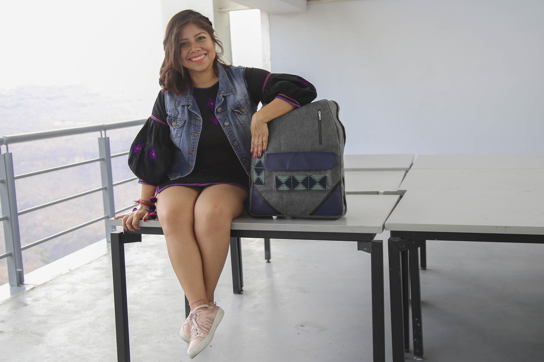 Nancy Gabriela Rojas Juárez, egresada de la licenciatura en Diseño de Modas del CUAAD; Modelando en una de las mesas de trabajo del centro universitario, una mochila diseñada por la misma que rescata tradición textil wixárika.