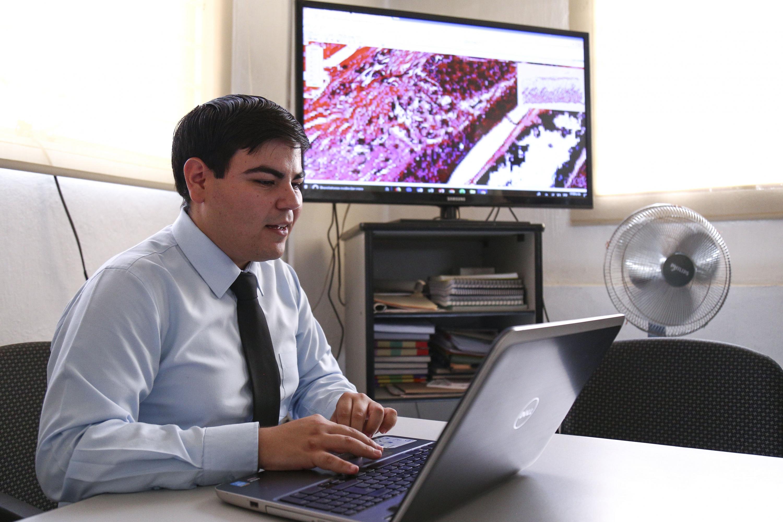 Estudiante del CUCS, operando una computadora para observar imágenes de tejido humano de manera virtual.
