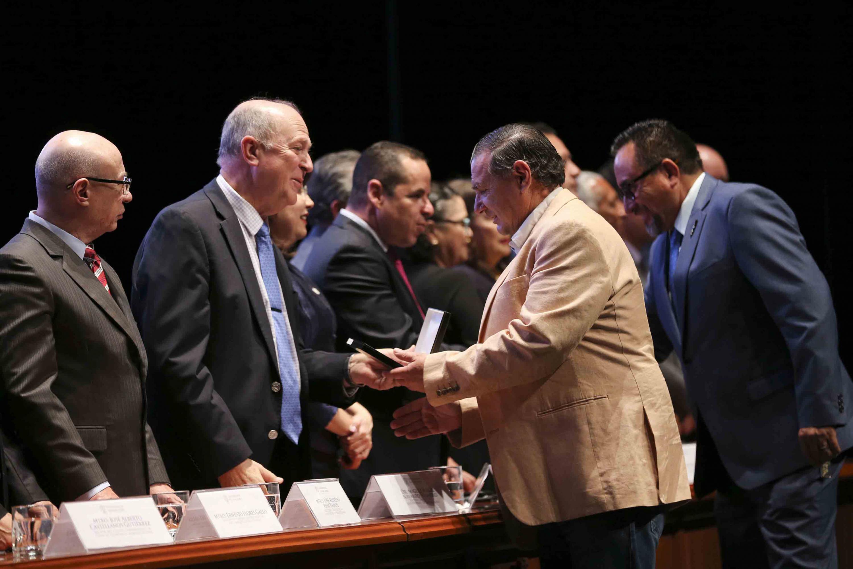 Rector General de la UdeG, doctor Miguel Ángel Navarro Navarro haciendo entrega de reconocimiento a un maestro