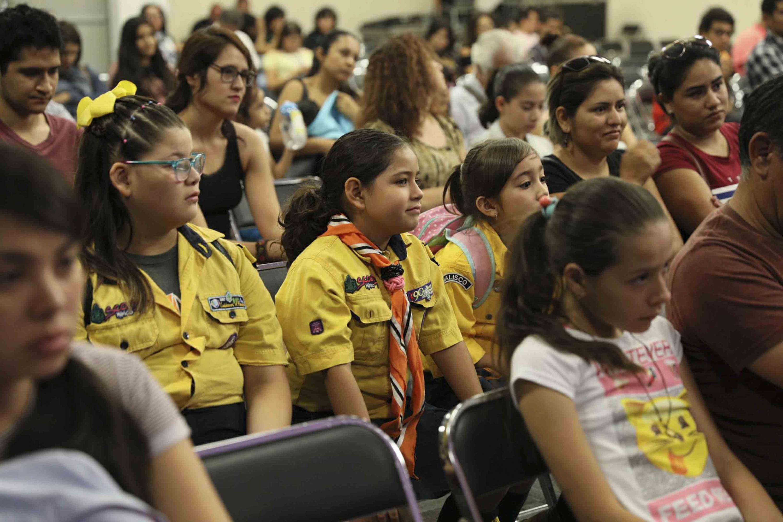 Adultos, jóvenes y niños asistentes al panel, escuchando con atención.
