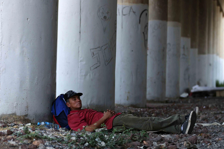 Persona en situación de calle, dormitando bajo los pilares de un puente.