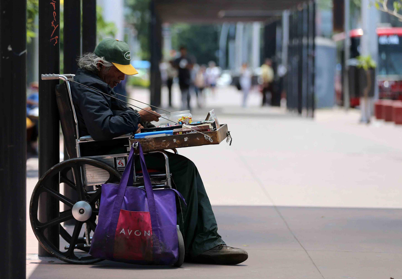 Persona de la tercera edad en situación de calle y en silla de ruedas, vendiendo dulces por el centro de la ciudad.