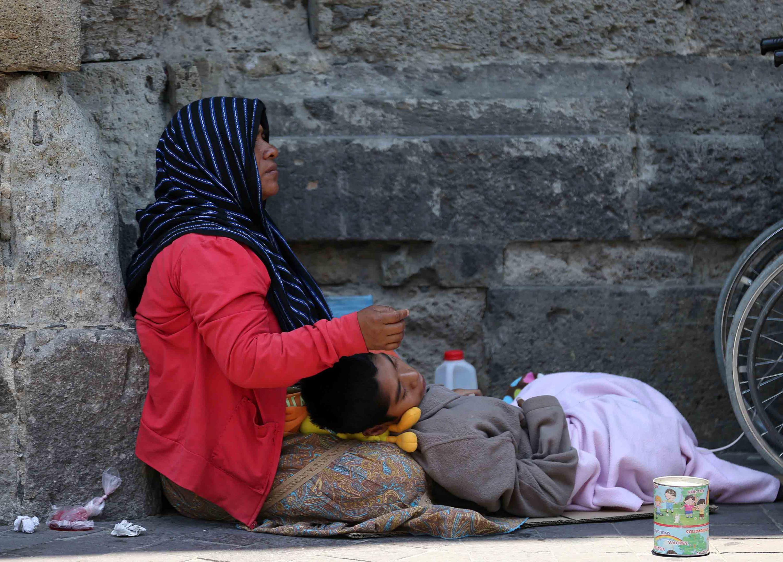 Señora en situación de calle y con niño enfermo dormido bajo su regazo, pidiendo limosna en el centro de la ciudad.