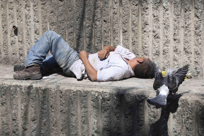 Persona en situación de calle, dormido bajo un monumento construido en la ciudad.