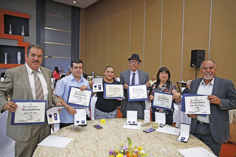 Seis trabajadores universitarios muestran su reconocimiento impreso de antigüedad en la UdeG