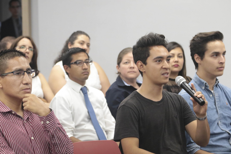 Un joven asistente haciendo una pregunta a la conferencista