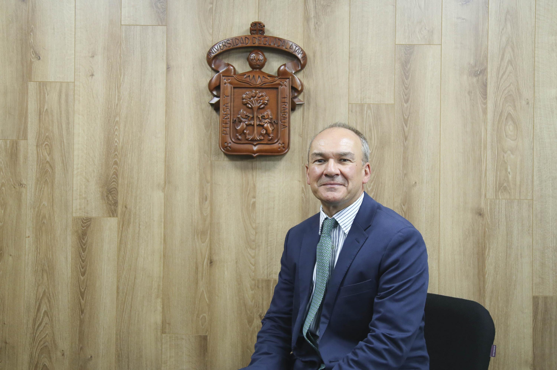 Tom Hockaday, sonriendo para la cámara, con el escudo de la Universidad de Guadalajara a sus espaldas.