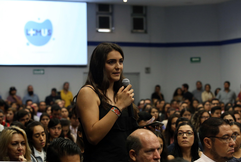 Una joven del público hace una pregunta al candidato invitado