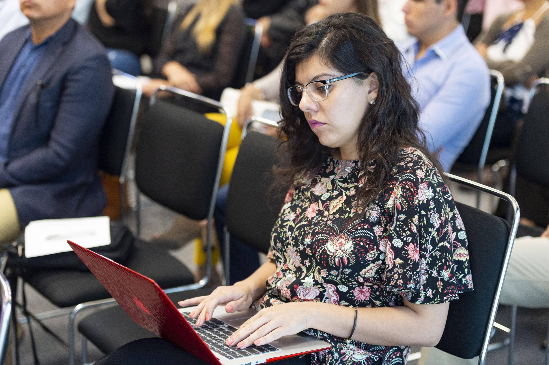 Mujer asistente al foro, manipulando su laptop, durante evento.