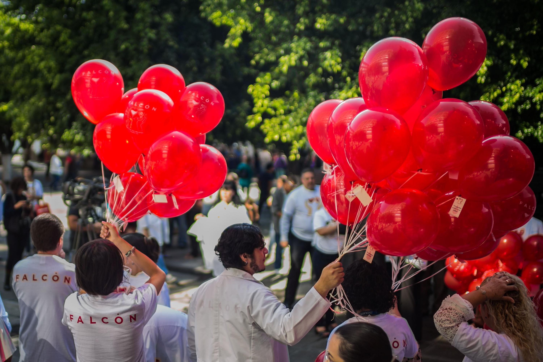 Algunas personas sostienen los globos rojos que fueron liberados en el evento.
