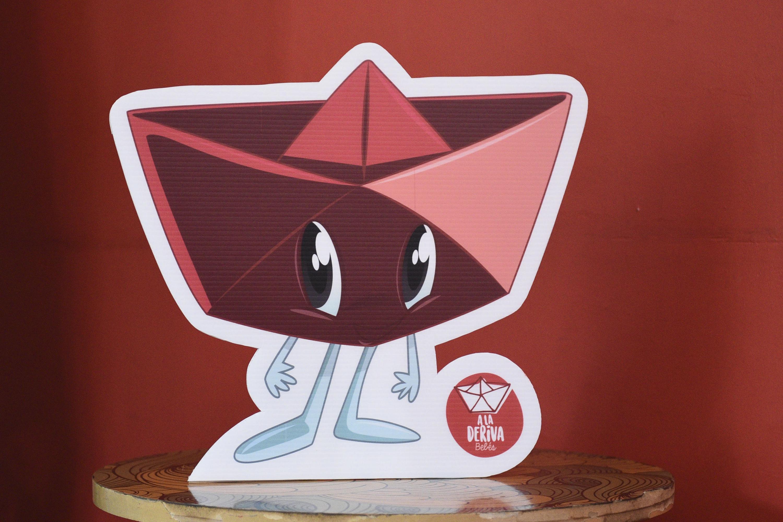 Mascota que fungirá como enlace de comunicación con el público; se trata de la personificación de una barquita de papel,