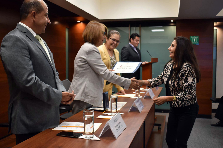 Rectora de UDGVirtual, doctora María Esther Avelar Álvarez, haciendo entrega de reconocimiento a trabajadora administrativa