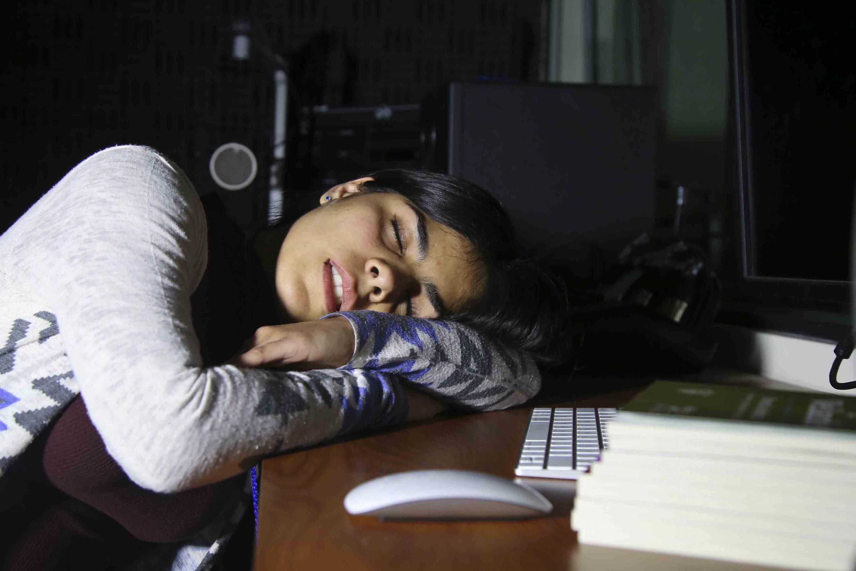 Joven durmiendo en un escritorio