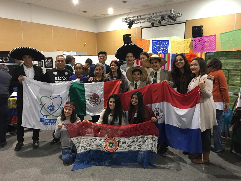 Estudiantes de bachillerato participantes en el proyecto, mostrando su bandera de procedencia; dentro de la feria del ambiente Eco Ciencias de Concordia en Argentina.