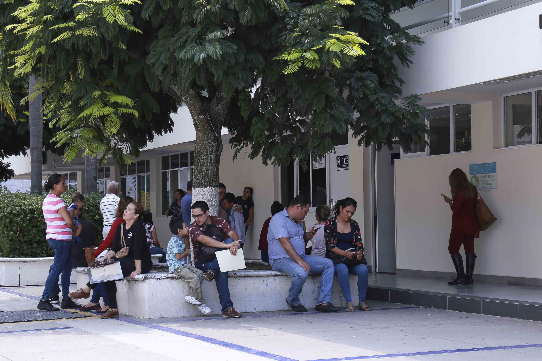 Un grupo de padres de familia sentados en las jardineras del edificio Ñ del CUCS.