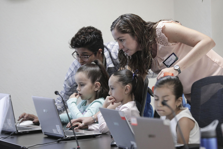 Las instructoras de los talleres de la Semana Nacional de NIÑASTEM PUEDEN, ayudando a unas niñas.