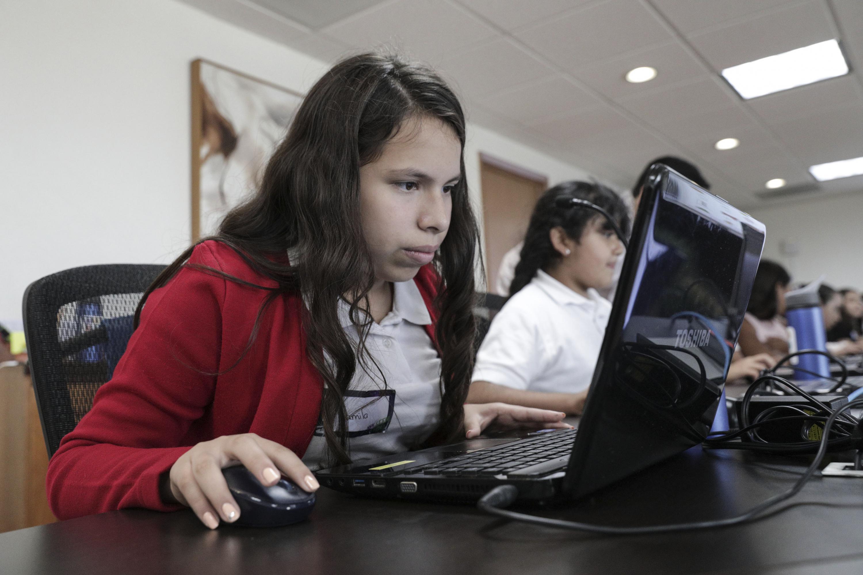 Niña participando en las actividades de los talleres; trabajando en computadora.