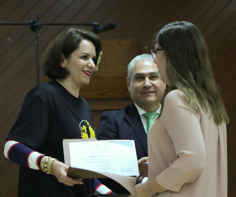 Maestra Esther Cisneros Quirarte, representante del Voluntariado del Hospital Civil de Guadalajara y presidenta de la Fundación Voluntarias contra el Cáncer A.C, haciendo entrega de reconocimiento