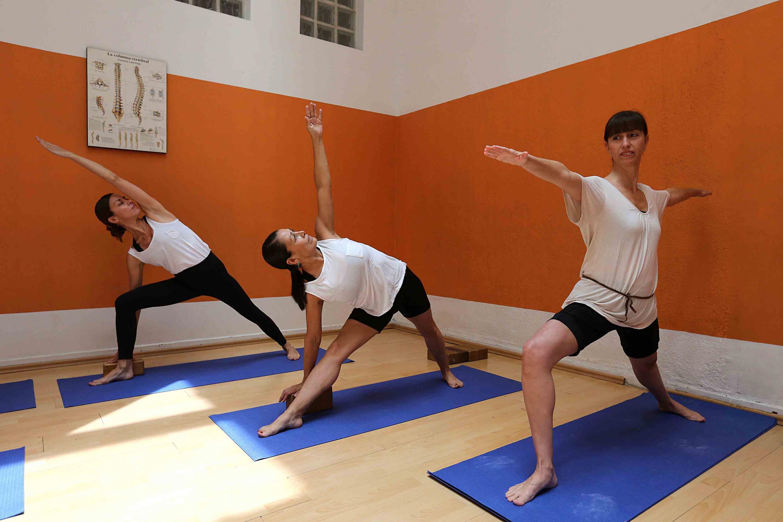 Tres yogistas en distintas posiciones de yoga