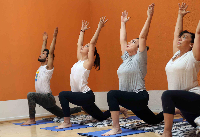 Grupo en posición de Yoga llamada Saludo al Sol