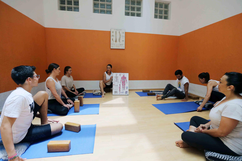 Una instructora explica a su grupo los principios del Hatha Yoga