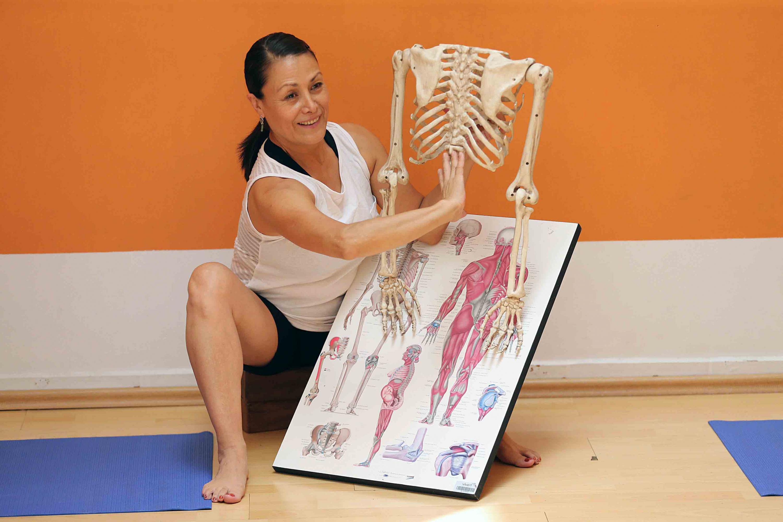 La instructora de Hatha Yoga muestra un poster con los nervios y musculos del cuerpo humano