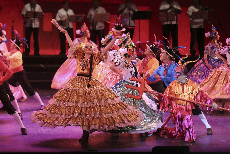 Un bailarin ataviado como diablo acompaña al ballet femenino