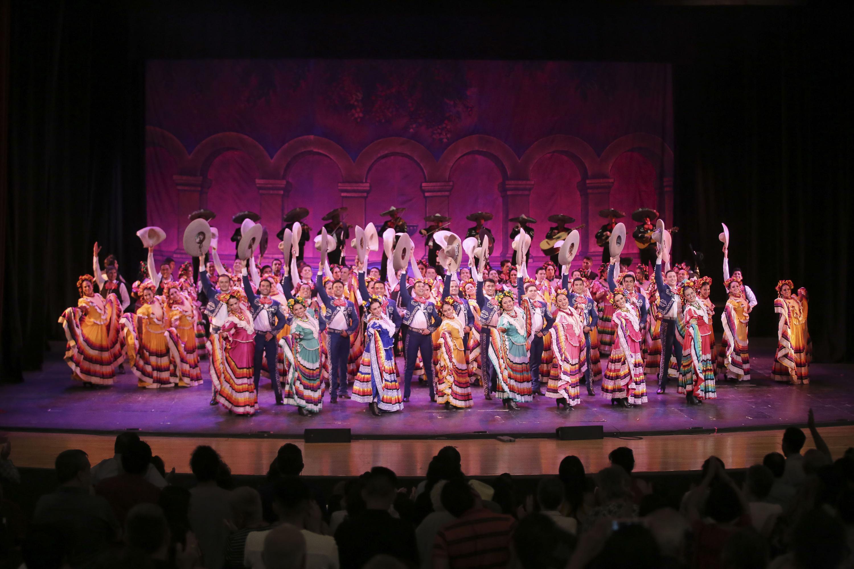 Todo el elenco del Ballet Folclorico de la UdeG saluda a la audiencia del teatro