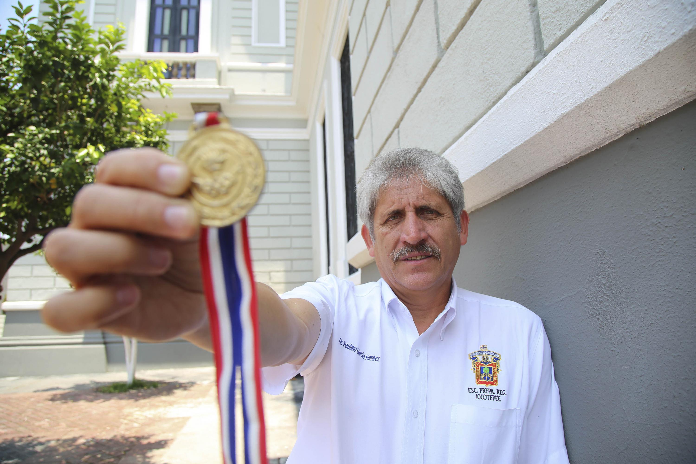 Doctor Paulino García Ramírez, profesor de la Preparatoria de Jocotepec de la UdeG, mostrando su medalla de oro.