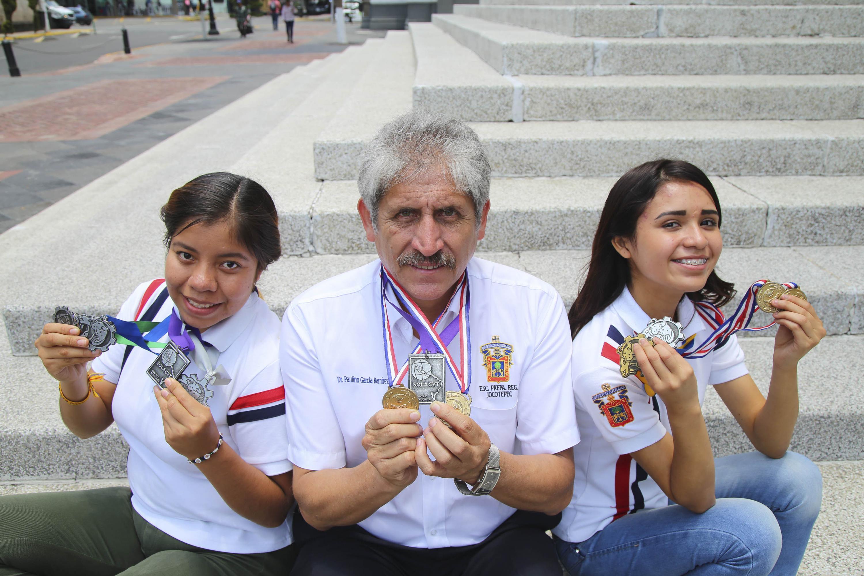 Profesor y dos estudiantes de la Preparatoria de Jocotepec de la UdeG, mostrando sus múltiples medallas en diferentes categorías.