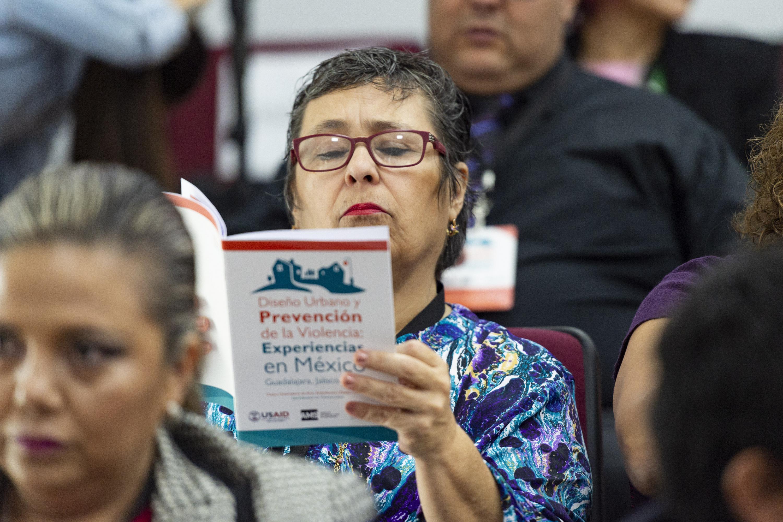 Una señora del publico lee la publicación entregada durante la presentacion