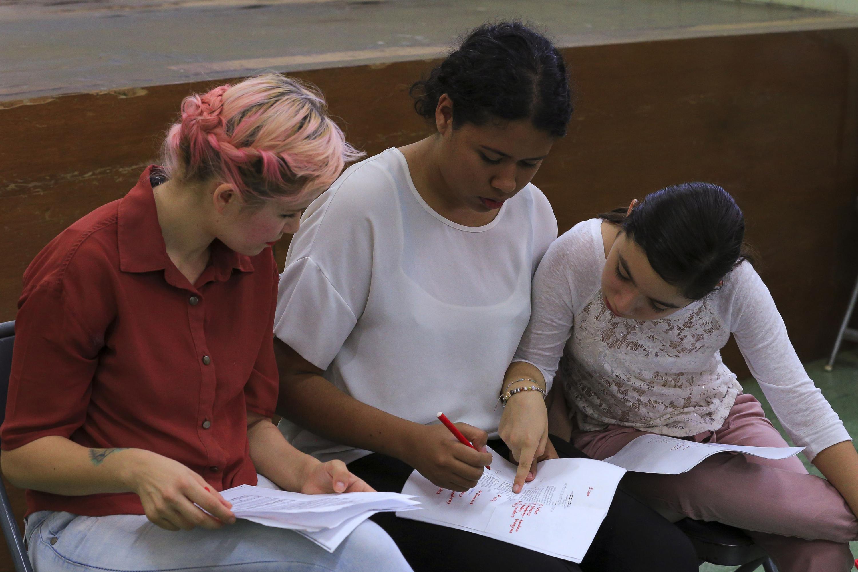 Tres jovenes del coro leen la letra del Himno durante el ensayo