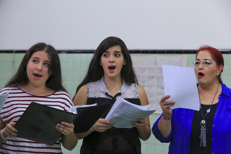 Una mujer y dos jovencitas cantando en el ensayo