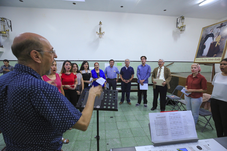 El director del coro dirige los ensayos para el aniversario luctuoso de Fray Antonio Alcalde