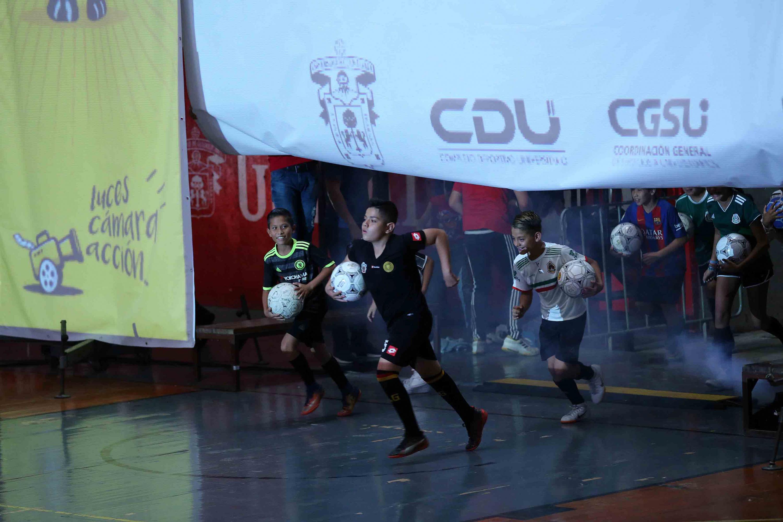 Niños participantes en el curso de verano de futbol, con pelota en mano; saliendo corriendo tras bambalinas hacia el escenario principal del Complejo Deportivo Universitario (CDU).