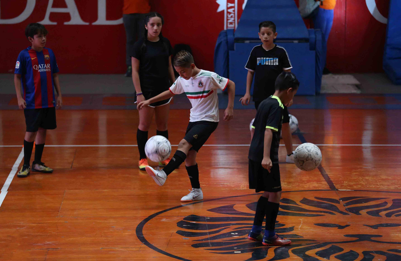 Niños participantes en el curso de verano de futbol, demostrando en escenario del complejo deportivo, su dominio de la pelota.