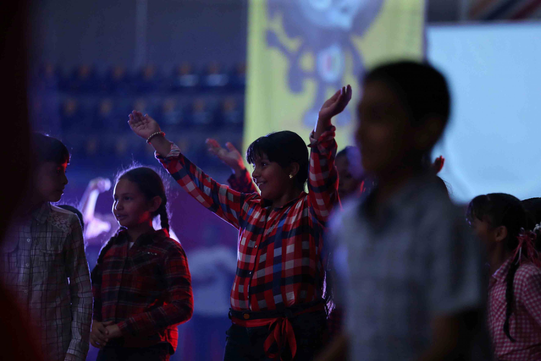 Niñas participantes en los cursos de verano del complejo deportivo, alzando las brazos hacia arriba.