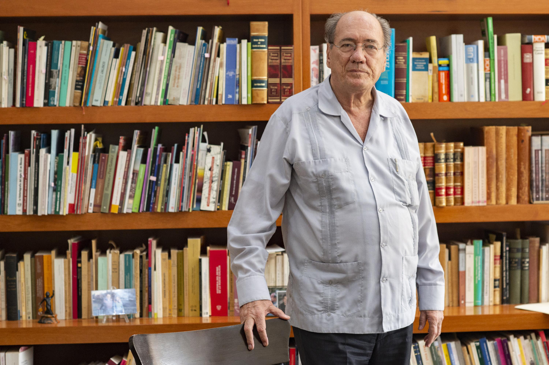 El historiador José María Muri de pie junto al escritorio y dos grandes libreros atras
