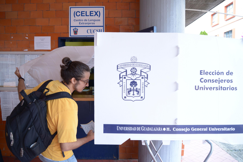 Estudiante entrando a una mapara para emitir su voto