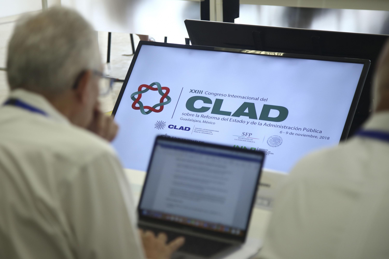 Uno de los asistentes al simposium trabaja en su laptop. De fondo se ve el logotipo de CLAD